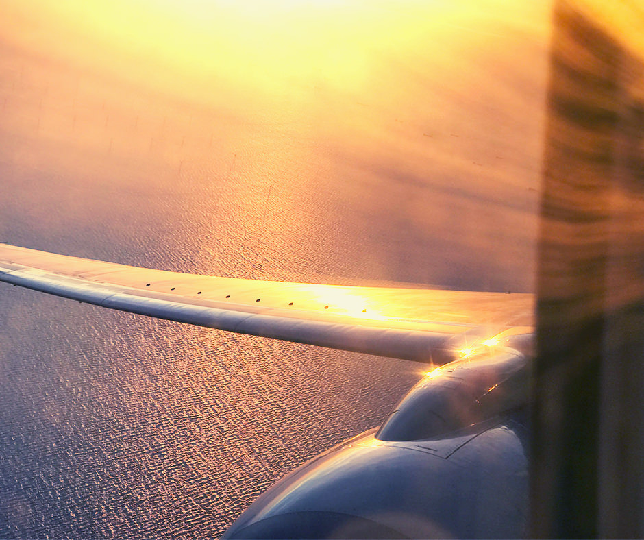 View out of an airplane window of the airplane wing flying over the ocean lit by sunset – looked out upon by a United Mint Campus Gap Year student heading to Spain.